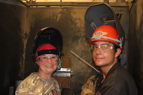 Senior Welding Instructor Elaine Waters embedded in the Ingalls Shipyard with GTS and Walton High School graduate Evan Corn