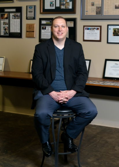 Ryan Blythe in professional clothes sitting on a stool.